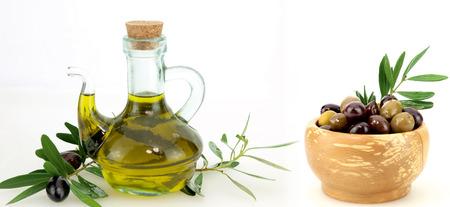 Olive oil and black olives on white background