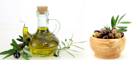Olive oil and black olives on white background