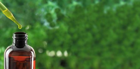 Dropper over essential oil bottle on green background