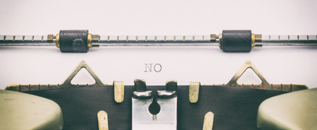 Close-up of word NO on a typewriter sheet