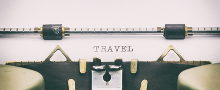 Close-up of word TRAVEL on typewriter sheet