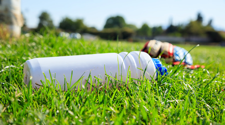 Soccer (football) water bottle on the green field