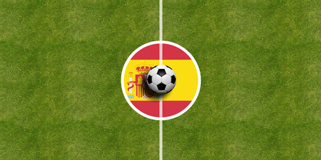 Spain flag on a soccer field center, top view