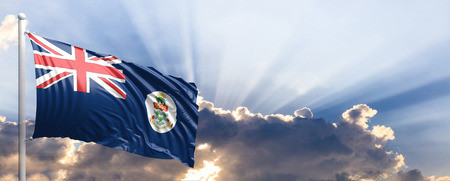 Cayman Islands waving flag on blue sky. 3d illustration
