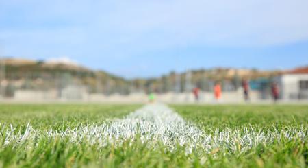 Close-up van geschilderde grenslijn van een groen voetbalgebied. Wazige spelers,