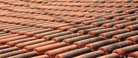 Old roof covered with ceramic tiles with black spots of brown color. Closeup.