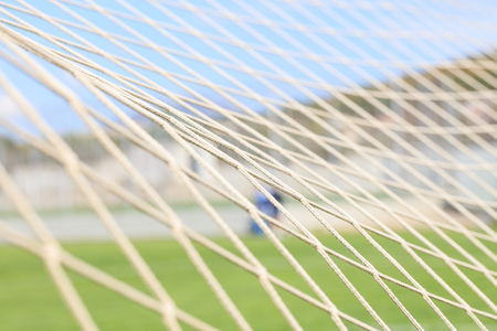 Soccer or football net background, view from behind the goal with blurred stadium and player.
