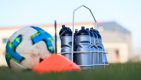 Ecological sport bottles of fresh water, beverage on soccer field grass. Blurred soccer ball, cone.