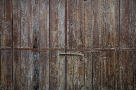 Wooden brown door. Weathered blank, banner, background with rusty latch and padlock. Closeup, detail