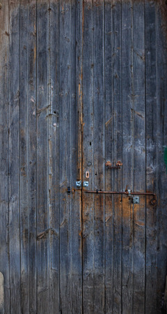 Wooden dark blue, blank, aged, peeled door for backdrop. Rusty latch on doorway. Close up, banner. Stock Photo