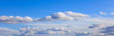 Blue sky backdrop with hanging colorful clouds on it. Aerial panoramic photo. Space for text, banner