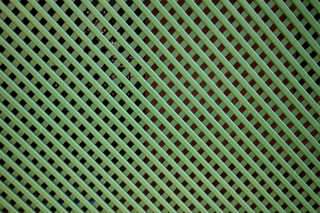 Green grid fence, weaving cross, blank for backdrop. Close up with details, space for text, banner