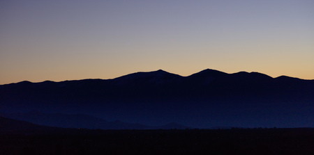 Sunset or sunrise over mountains silhouette with blue sky backdrop. Panoramic view, banner. Stock Photo