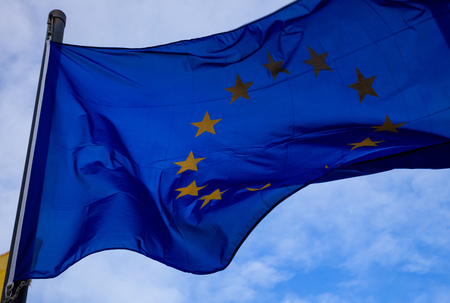 Eu flag waves proudly on flagpole, with blue sky and clouds for background. Closeup with details