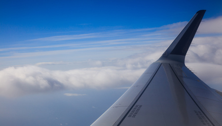 Blue sky, fluffy clouds from planes window for backdrop. Aerial, space for text, panoramic, banner.