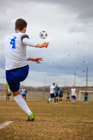 Football player on arena kicks the ball during soccer match. Blur team, sky backdrop, behind photo