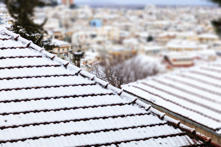 Rooftops full of white, soft snow. Winter, time for holiday. Blur town background, close up, details