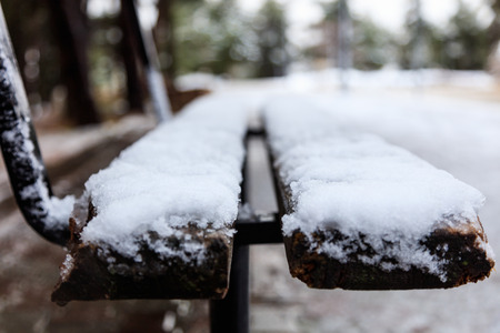 Lonely bench, covered with snow in a park waits for companionship. Close up, detail, blur background