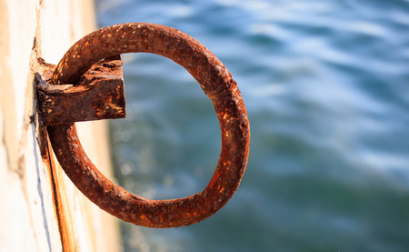 Old rusty bollard waits at quay for boat to be tied. Blur sea for backdrop, closeup, details, banner