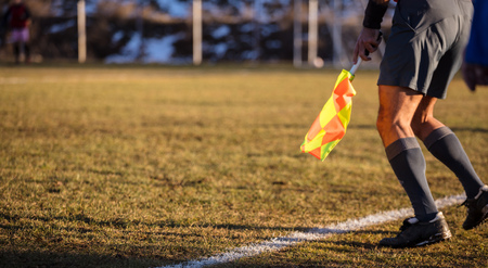 Football soccer arbiter assistant moves at sideline observing the match with flag at hands. Blurred green field and nature background, close up view, banner, space.