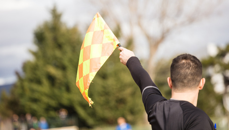 Football soccer arbiter assistant observes the match and raises the flag with his hand. Blurred blue sky, nature, players background, close up view, details. Stock Photo