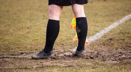 Football soccer arbiter assistant stands at corner side with shoes full of mud and flag at hands. Blur green field background, close up.