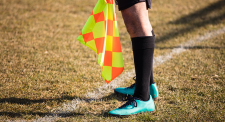 Football soccer arbiter assistant stands at sideline observing the match with flag at hands. Blurred green field background, close up. Stock Photo