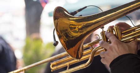 Musician with brass trumpet plays, pressing the valves with his fingers, classical music. Close up view with details, blurred background. Foto de archivo