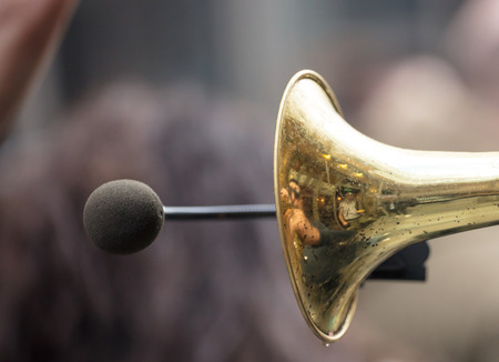 Brass trumpet, front side with microphone for loud sound.Peoples reflection on it.Close up view with details, blurred background.