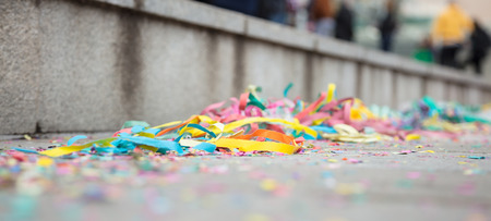 Carnival party with colorful serpentines on street. Blurred pavement background. Close up view, banner, space for text. Stock Photo