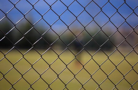 Wire metallic mesh fence around a football field. Blurred green grass, blue sky and trees background, close up view with details.