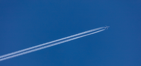 Airplane with white trace behind it. Diagonal direction, blue cloudless sky backdrop, banner, under view, space for text.