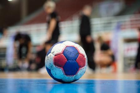 Balón de balonmano en el piso de la cancha. Listo para el partido. Árbitros, entrenadores y atletas borrosos y antecedentes de campo.