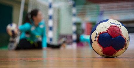 Handball ball on court floor. Blurred female goalkeeper repulse the attack background. Space for text, close up view. Stockfoto