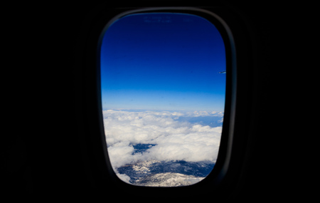 White clouds background hanging on blue sky and covers snowy mountain. Aerial photo from airplanes window. Black background Stock Photo