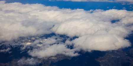 White heavy clouds background hanging on blue sky over mountain. Aerial photo from airplanes window.