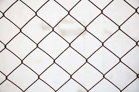 Wire mesh fence made of steel with white blurred background. Close up view with details.