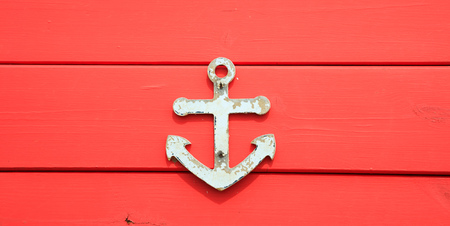 Anchor symbol on aged surface. Peeled sign, red blank board background, close up view.