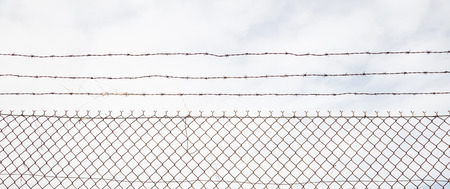Wire mesh fence made of steel with cloudy sky background. Close up view with details, banner.