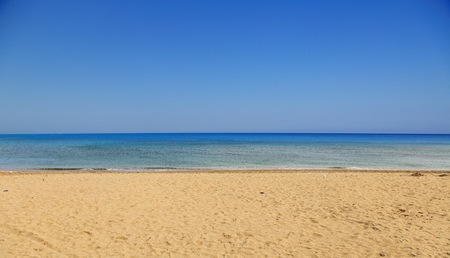 Sandy beach, calm sea, clear blue sky background. Summer destination for holiday and relaxing.