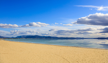 Sandy beach, calm sea, blue sky with few white clouds background. Summer destination for holiday and relaxing. Reflection on sea of clouds and mountains. Stock Photo