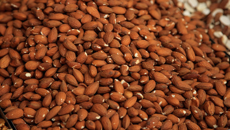 Almondss kernel proper snack for vegan, vegetarian and people on diet. Natural, healthy and nutrient brown nuts background. Top view.