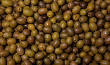 Shiny green olives background. Healthy fresh snack. Closeup, top view.