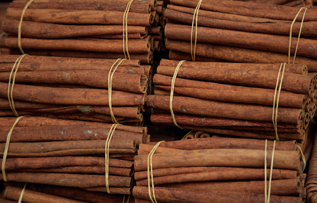 Cinnamon herbal sticks on tied rolls. Canella natural brown aromatic spice background, top view, Stock Photo