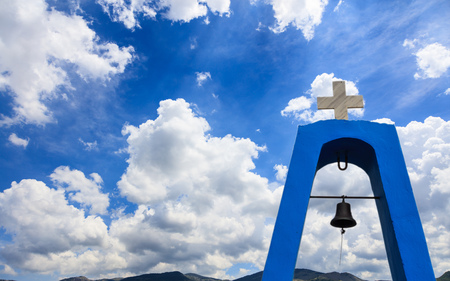 Churchs steeple in Greece. Cross on top and bell under it. White clouds on blue sky over mountains background, copyspace Stock Photo