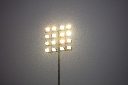Stadium lights on pole, outdoors, snowy night. Dark sky in contrast to intense lights.