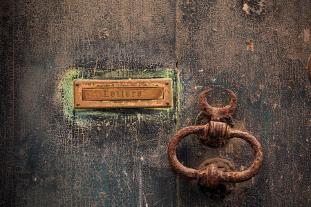 Wooden brown door background with rusty letterbox and doorknob. Timeworn closed entrance, close up view with details. Stock Photo