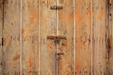 Wooden brown door background locked with rusty padlock. Timeworn, closed entrance provides safety and privacy. Close up view with details. Stock Photo