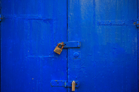 Wooden blue door background locked with two rusty padlocks. Old, closed entrance provides safety and privacy. Close up view with details. Stock Photo