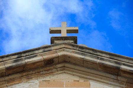 St John Baptist chapel in Malta. White cross on the top of a limestone building. Blue sky with clouds background. Religious destination.